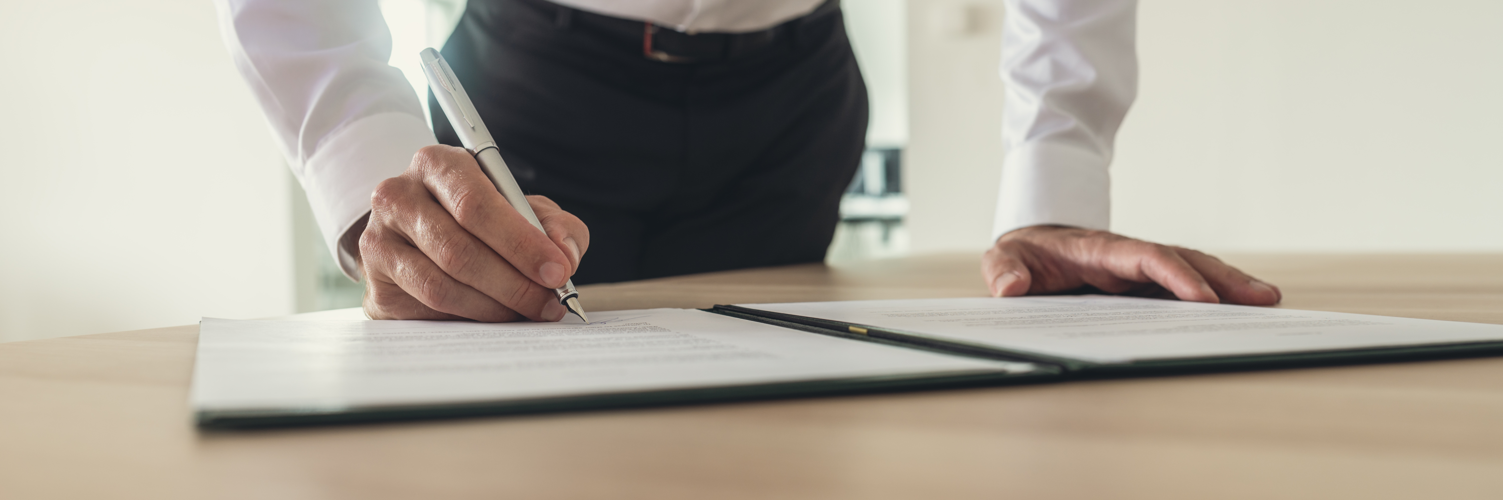 businessman-signing-contract-QRS6KLM