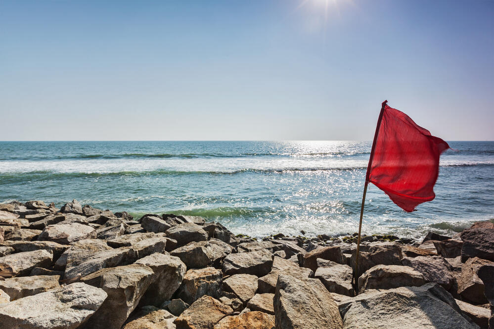 red-flag-on-rocky-beach-ZVAGXNE